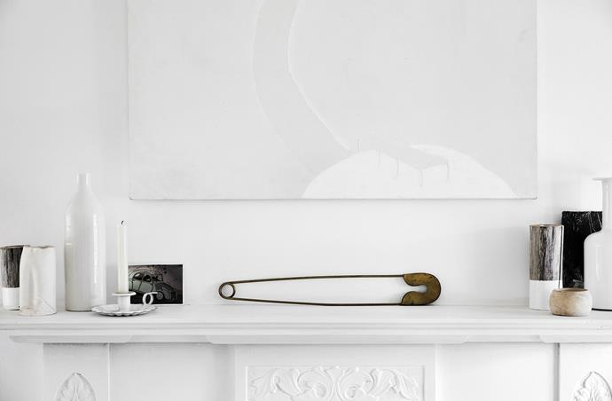 """Homeowner Louella Boitel-Gill describes this spot as a """"mantel curated with treasures, an oversized brass safety pin and postcard of my Citroën 2CV. One of my own paintings hangs over the mantel."""""""