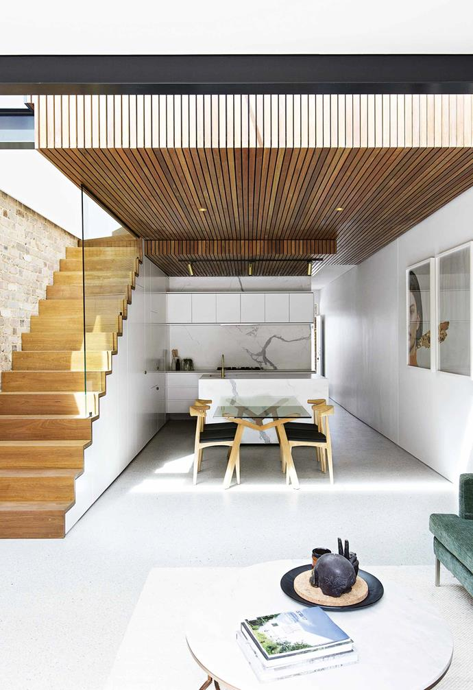 """The timber cladding wraps around the box so that it appears to float. """"You see the material wrap from the kitchen ceiling through the living area's glazed roof and run up the exterior rear wall,"""" says Michael. He repeated the box shape throughout, with joinery to suit. """"Everything ties in,"""" says Casey. """"We love it.""""<br>,br>*Living area** The staircase makes a striking backdrop to the dining area. """"Because it sits right in the middle of the living zone and kitchen, it had to be a pretty big focus,"""" says Casey. The glass wall disappears to create the illusion of hanging stairs. The area beneath the stairs is kitted out with kitchen and dining storage, as well as the fridge and laundry. """"I love how everything is concealed,"""" says Casey. """"This one whole wall just looks like the staircase, but everything is there."""""""