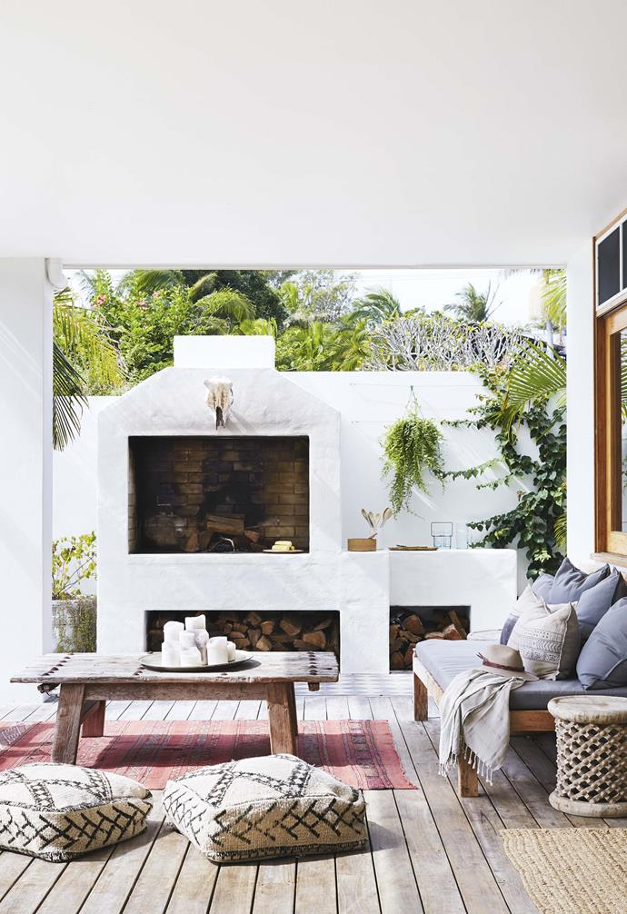 "On the outdoor deck of this [all-white Byron Bay abode](https://www.homestolove.com.au/relaxed-all-white-byron-bay-home-with-upcycled-details-19266|target=""_blank""), a stunning outdoor fireplace and oven was created to help keep this space cosy all year long."