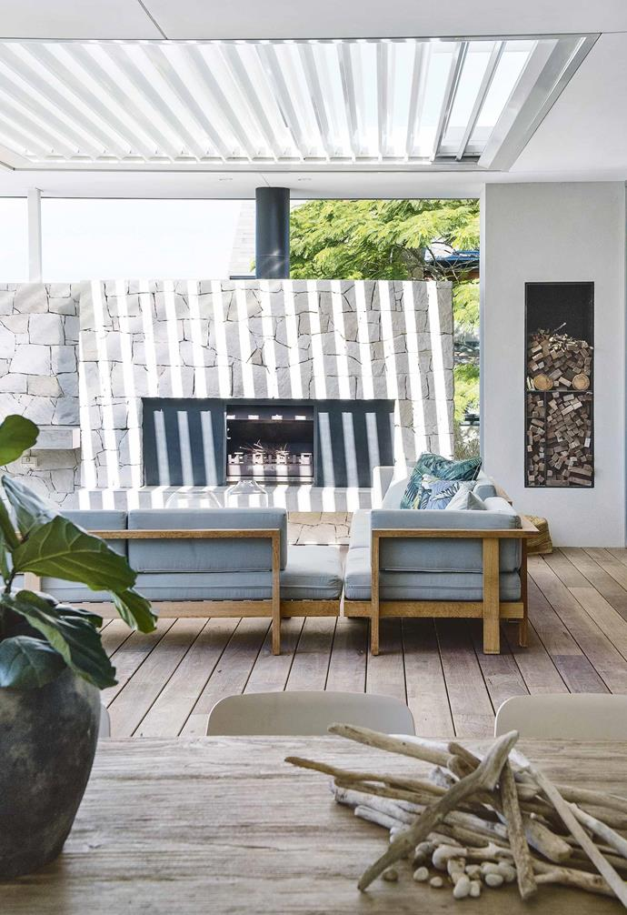 "In the outdoor room of this [contemporary Perth home](https://www.homestolove.com.au/contemporary-eco-friendly-home-perth-17078|target=""_blank""), a generous stone-clad fireplace is the perfect gathering place for the whole family. A clever niche was added to the space to create a stylish and functional way to store firewood."