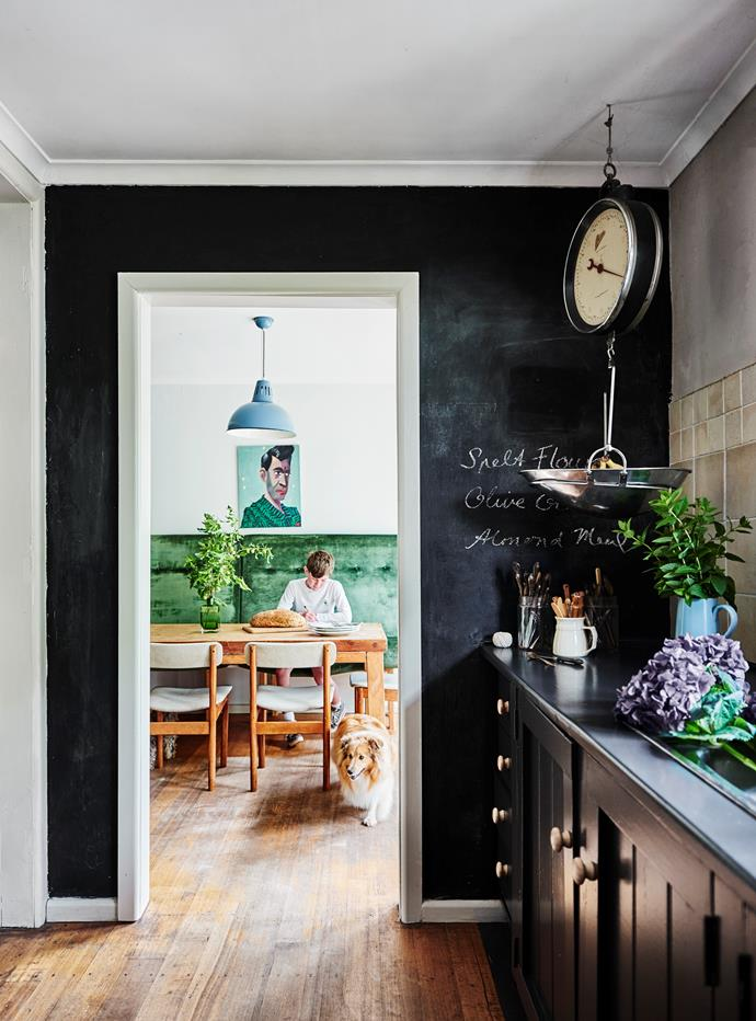 Vintage Brice scales are a feature in the kitchen. One wall is painted in chalkboard paint. Through the doorway, Henry is with Emmy.