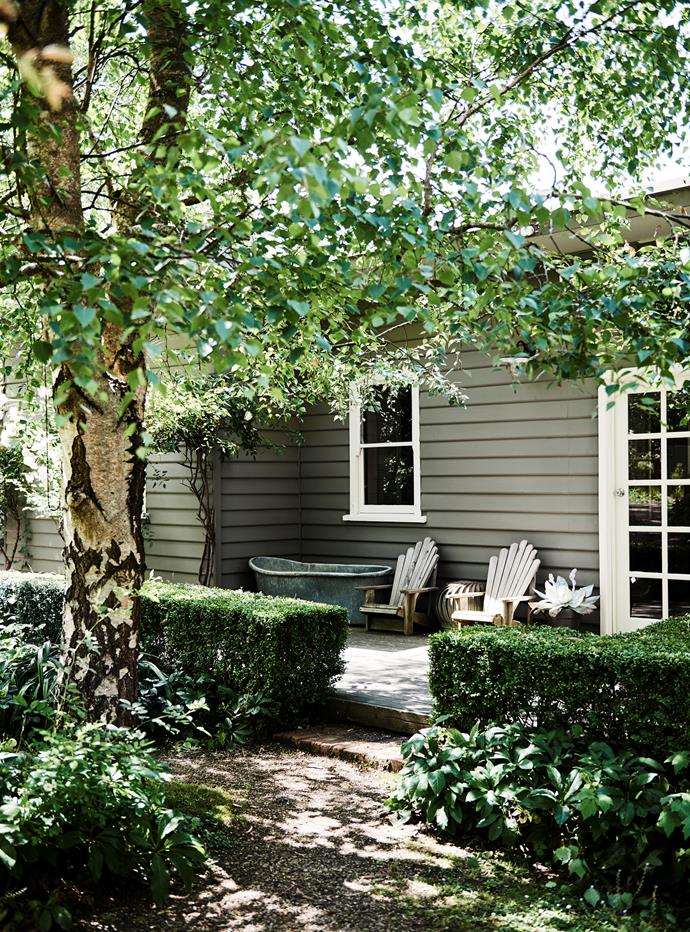 On the porch, an antique French galvanised bath sits beside chairs picked up at a flea market.