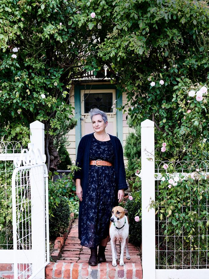Artist Anna Placidi with her loyal walking companion, Luigi, a whippet terrier cross, at the front entrance to her miner's cottage.