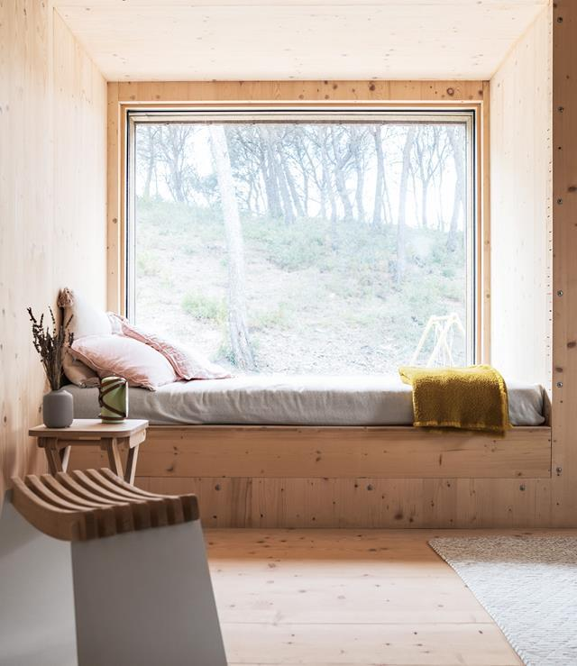 """Large windows let natural light flood onto this daybed, which is the perfect spot to take in the stunning landscape around this [Nordic-style cabin home](https://www.homestolove.com.au/nordic-timber-cabin-20476