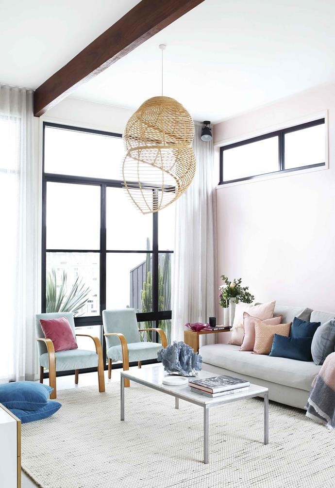 """A pastel pink feature wall adds warmth to the living room of this [Palm Springs-style home](https://www.homestolove.com.au/palm-springs-mid-century-casuarina-18340