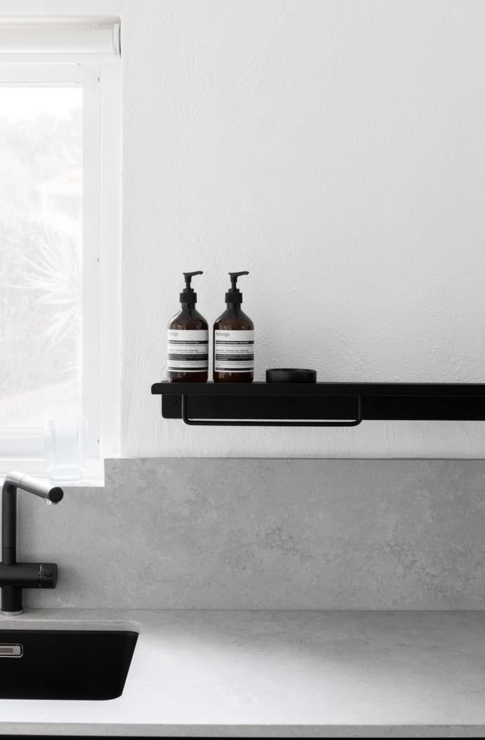 Caesarstone surfaces in Airy Stone and powder-coated steel fixtures carry through from the kitchen into the laundry.
