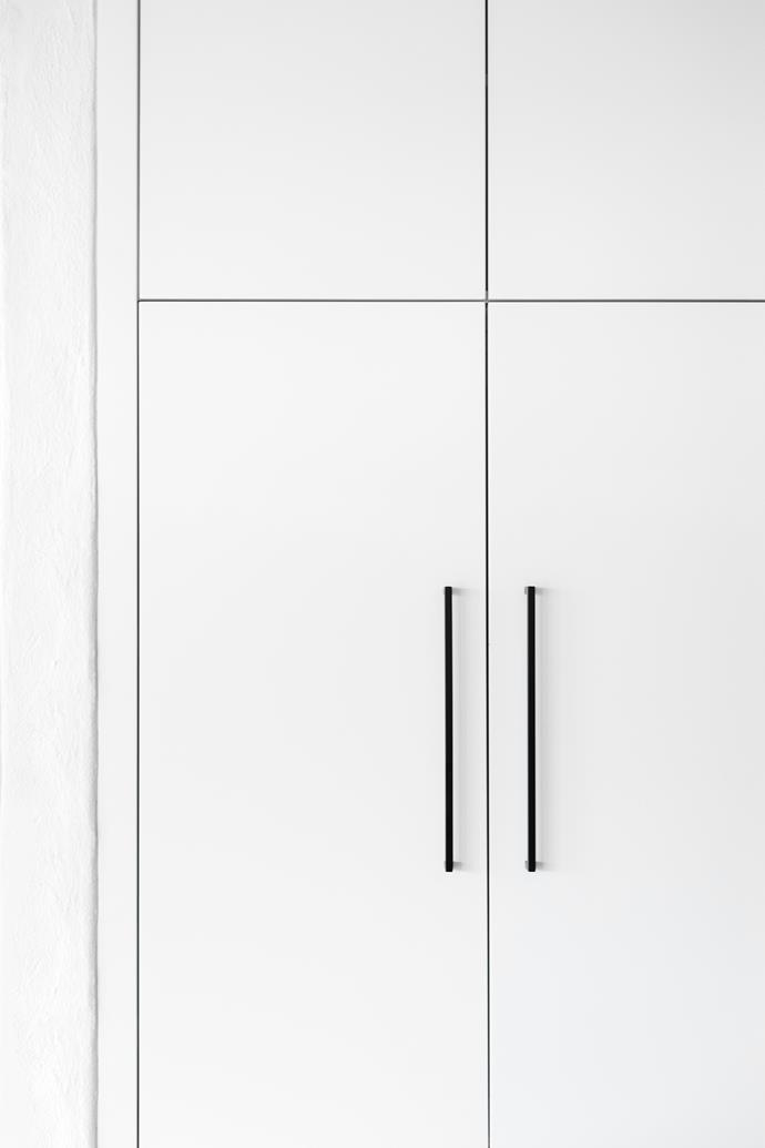 Matte black details – from the door handles, to the power points and even the kettle and salt and pepper mills – act in dramatic contrast to the all-white cabinetry, giving a contemporary spin to an otherwise classic look.