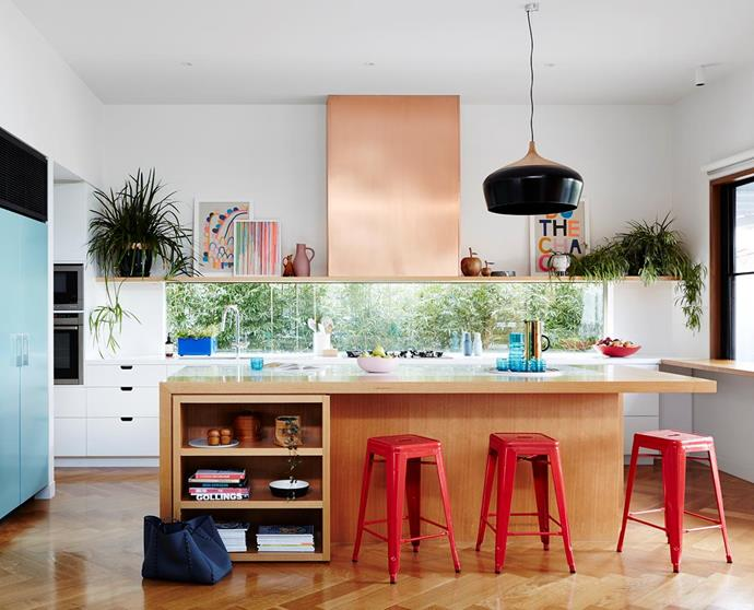 "Wooden cabinetry gets a fresh update in this [Melbourne modernist home](https://www.homestolove.com.au/colourful-kitchen-appliances-19988|target=""_blank""), with red stools, blue touches and a striking, streamlined copper range top."