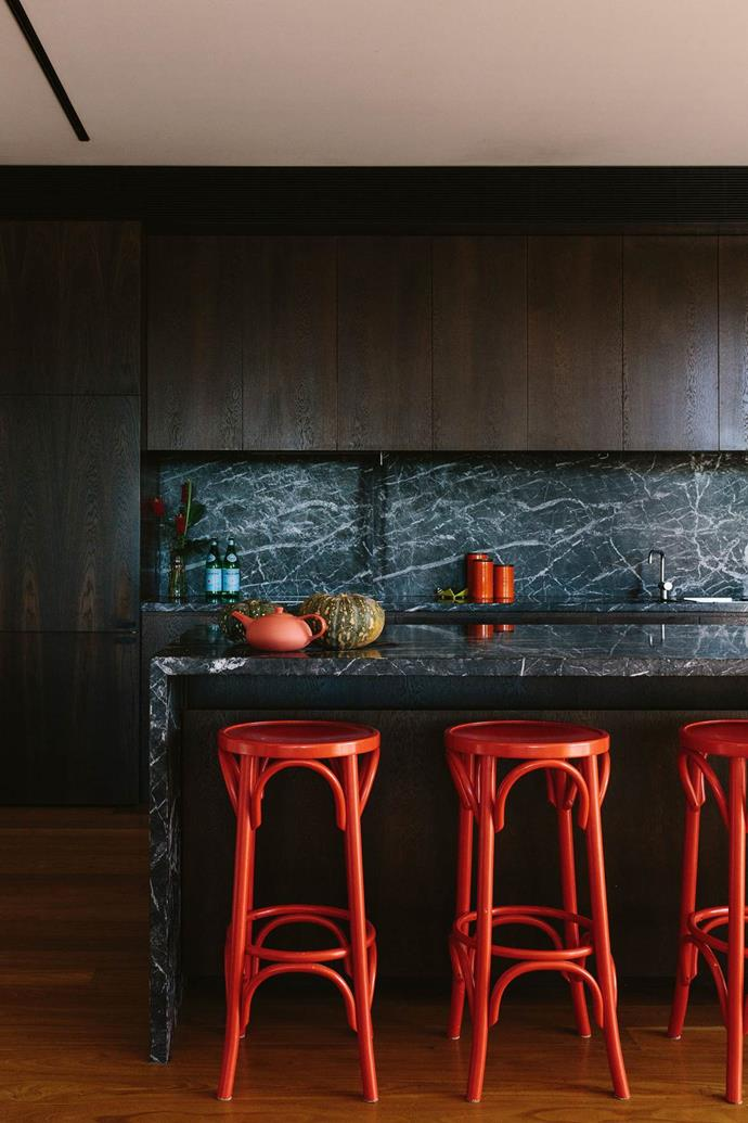 "Marble doesn't have to be white. This sophisticated, black kitchen with dark marble uses bright red stools to add a pop of colour, to suit this [modern lake house on the Mornington Peninsula](https://www.homestolove.com.au/modern-lake-house-design-13813|target=""_blank"")."