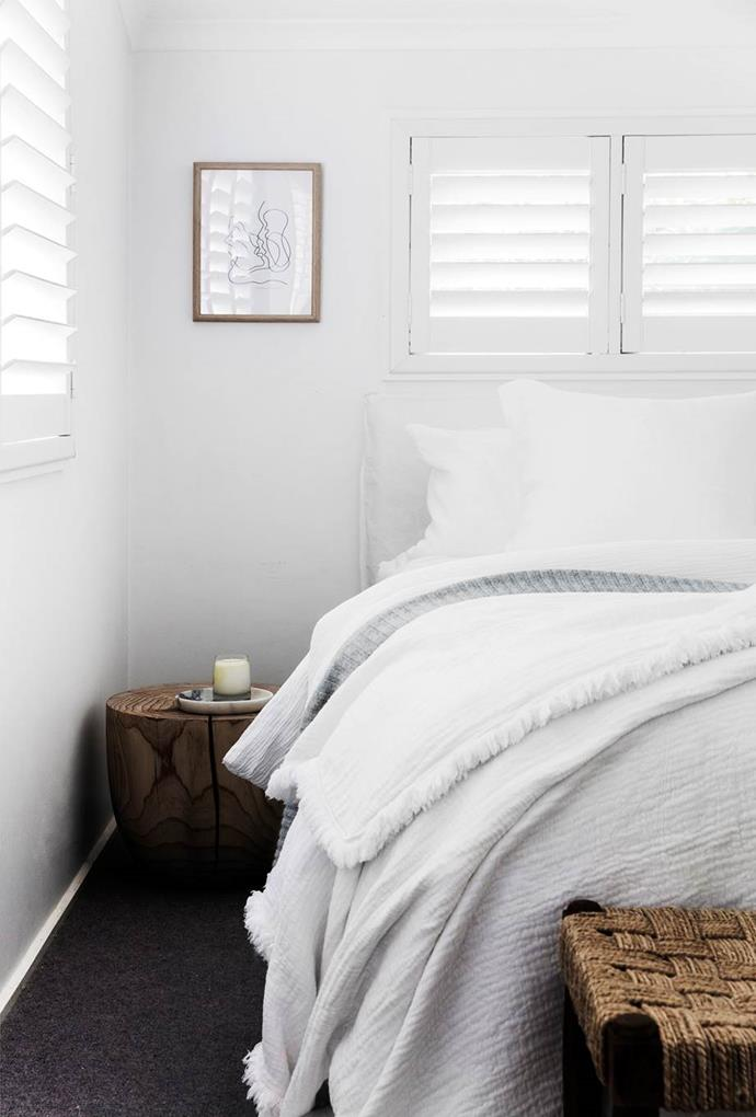 """Contemporary touches, such as a simple line drawing and a wooden tonk side table lend a sophisticated element to the relaxed aesthetic of this bedroom in a [stylist's minimalist home in Sydney's Seaforth](https://www.homestolove.com.au/minimalist-coastal-home-19515
