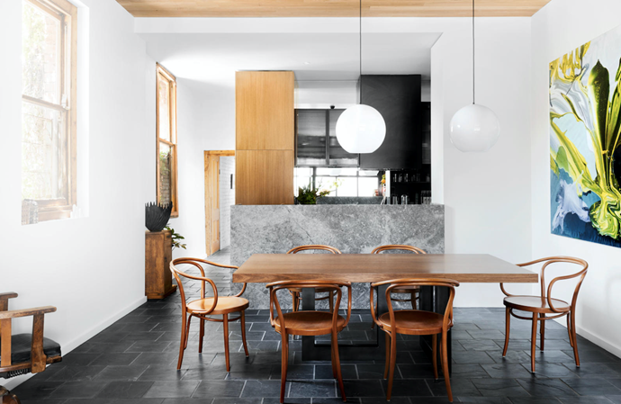 Benchtops in grey Aether marble. Melamine cabinetry in Cinder Matt, Polytec. Aggregato Sfera pedant lights, Artemide. Slate tiles, De Fazio Tiles and Stone. Artwork by Christina Popovici. B9 Le Corbusier chairs, Thonet.
