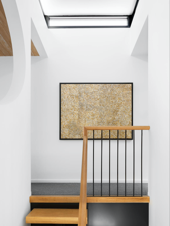 A skylight draws natural light into the core of the home. Artwork by Mary Rumble Petyarre. Stonefields carpet in Black Marble, Feltex Carpets.