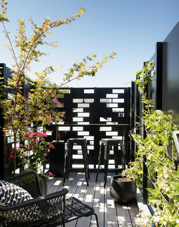 """The laser-cut screen, designed by Amanda and made by Idle Hands, takes its cues from the original brickwork. """"The cutouts are identical to those bricks in size and shape,"""" says Amanda. Stools, Thonet. Woven chair, Ikea."""
