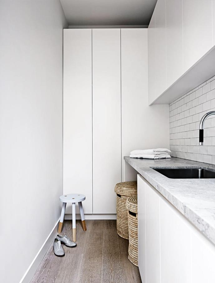 Tucked beside the butler's pantry, the laundry offers maximum storage thanks to custom joinery, though still benefits from lots of natural light via a window. The signature stone is also carried through this space.