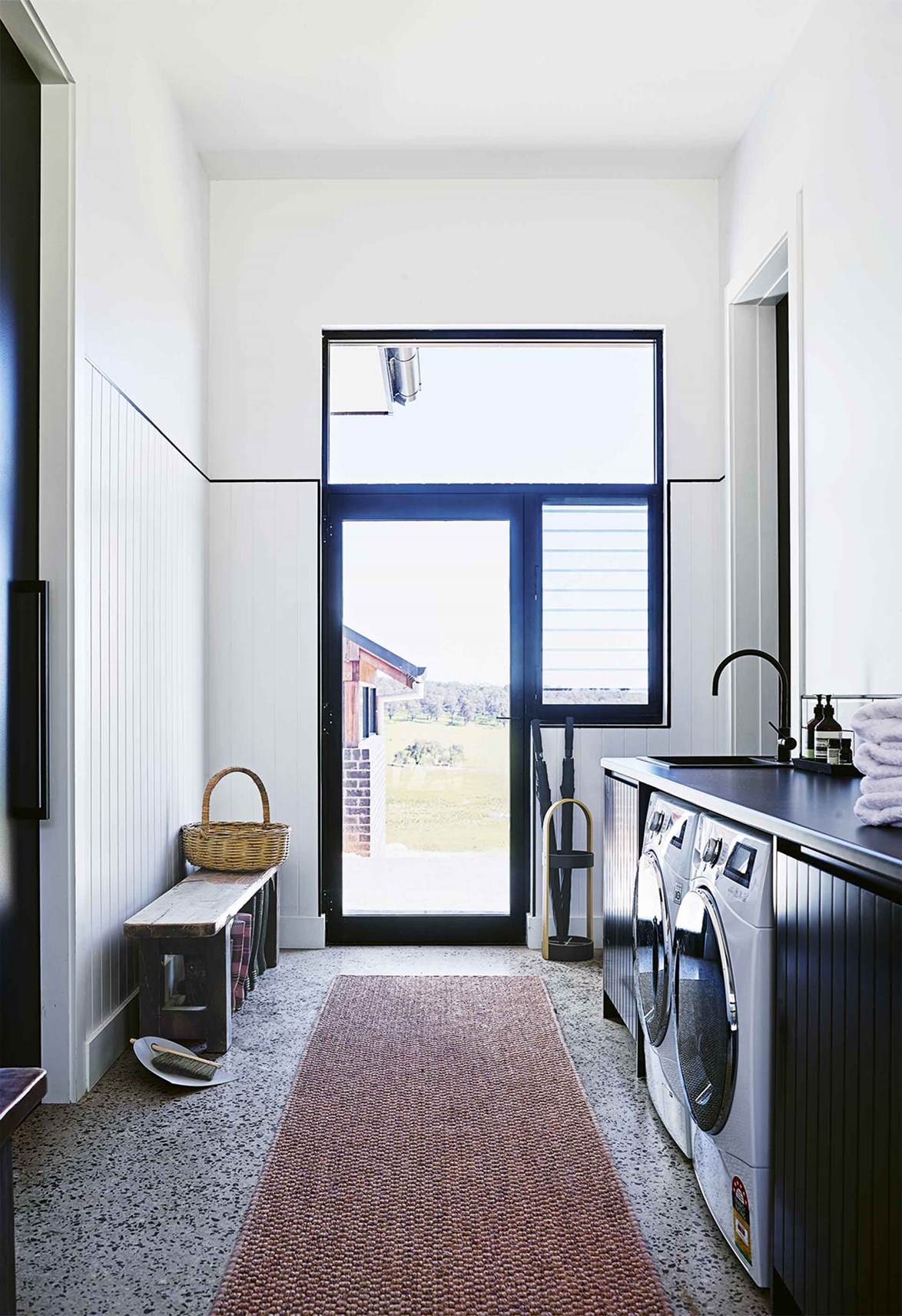 A modern farmhouse laundry with a washer and dryer positioned side-by-side.