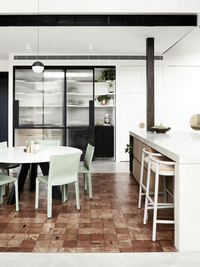 The butcher's block floor defines the dining area in the open-plan zone. Gebrüder Thonet Vienna GmbH 'Curve' barstools from Space. Flos 'String' pendant light from Euroluce.