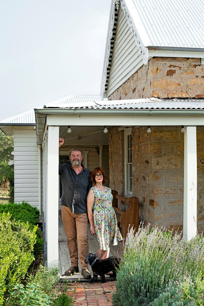 Artist Rowen Matthews with his wife Cathy Armstrong and Dixie the spoodle on the verandah of the original stone schoolhouse, now one of Rowen's studios.