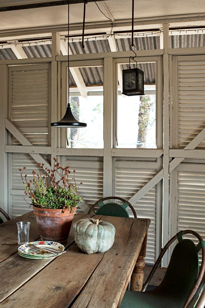 Rowen recycled shutters from the homestead to line the summer house, which is used as a dining room.