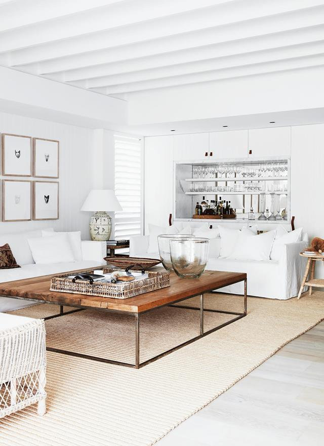"""Practicality, calmness and an affinity for neutrals underpin the chic aesthetic of this [coastal holiday house](https://www.homestolove.com.au/waterfront-abode-with-a-bahamas-inspired-aesthetic-20907 target=""""_blank"""") that offers a resort-style ambience. A built-in bar area in the light-filled living room contributes to the holiday vibe."""