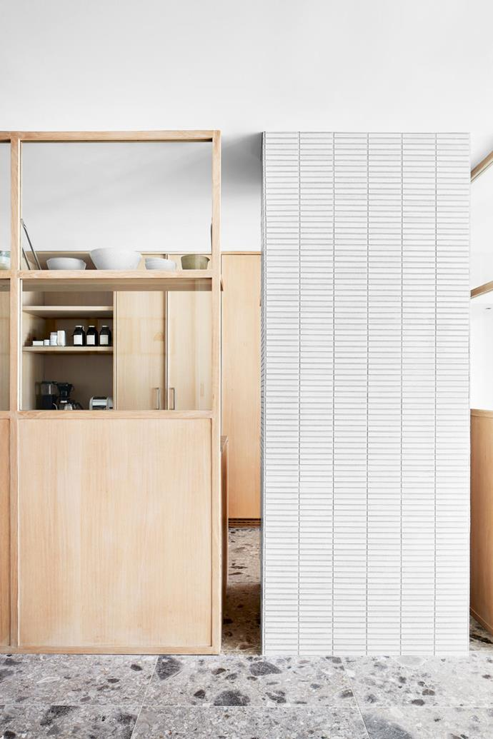 In the kitchen, suspended shelves display the owner's collection of ceramics. Eschewing unsightly joins, the kitchen cabinets are akin to freestanding furniture, set apart from a wall clad in Inax tiles from Artedomus.