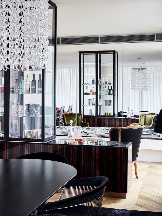 The glamorous spaces in this Melbourne apartment are large but rooms feel intimate and are defined using feature joinery elements such as the glass cabinet that serves as a bar.