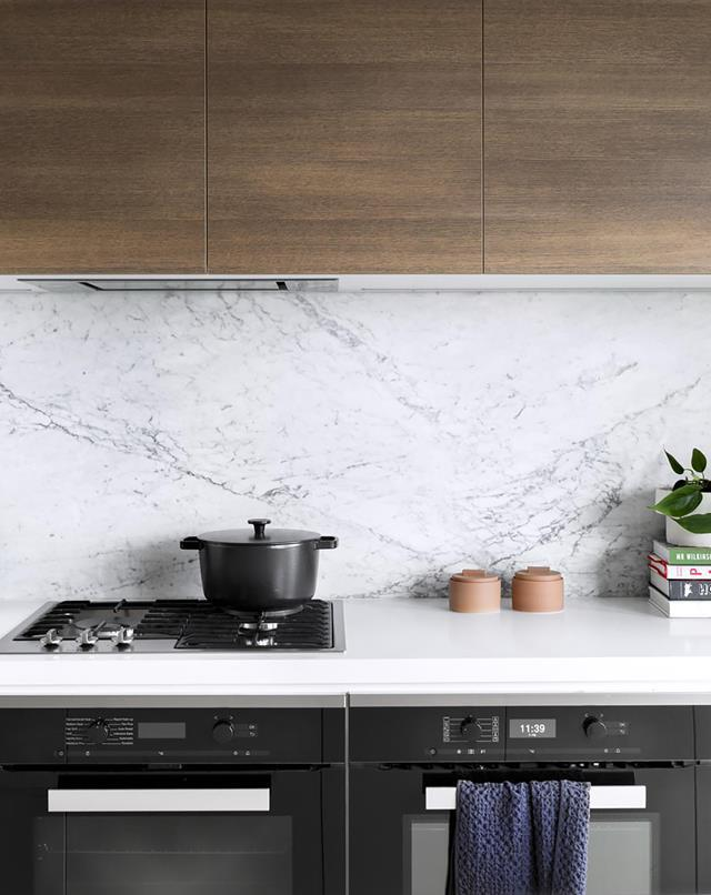 "When it came to building this [modern kitchen](https://www.homestolove.com.au/white-and-timber-kitchen-19832|target=""_blank""), the owners opted for Caesarstone Pure White benches."