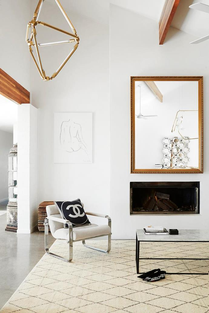 "This [1970s home with a Palm Springs](https://www.homestolove.com.au/oracle-fox-amanda-shadforth-home-20153|target=""_blank"") vibe in Brisbane has kept the living room pared-back with a minimalistic approach to buying designer and vintage finds and a streamline fireplace to add warmth."