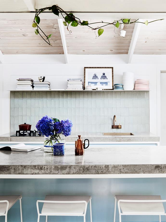 Baby-blue cabinets topped with concrete benchtops made by Damian make the heart of the home a show-stopping one.