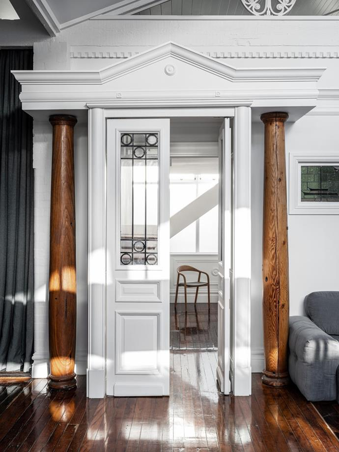 Looking through the portico from the living room to the hallway. Sofa from BoConcept. Artisan 'Neva' dining chair from Spence & Lyda. Walls painted in Dulux 'Vivid White'.