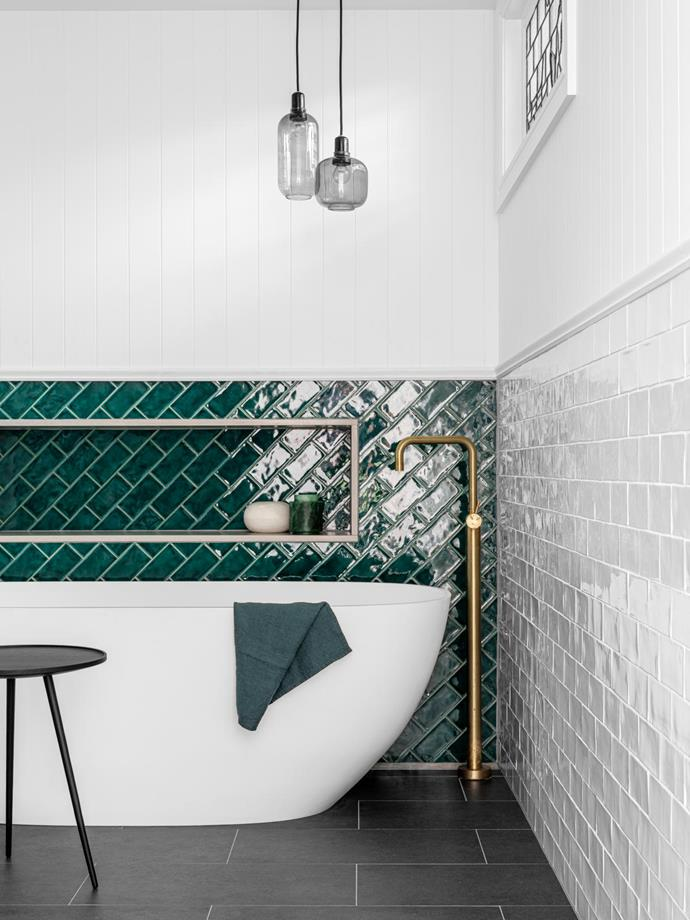 Kado 'Lussi' freestanding bath from Reece. Ligne Roset 'Linden' occasional table from Domo. Normann Copenhagen 'Amp' pendant lights from Huset. Scalafloor-mounted bath mixer in Brushed Brass from Reece. Charcoal floor tiles and glossy white and green wall tiles, all from Tiles By Kate.