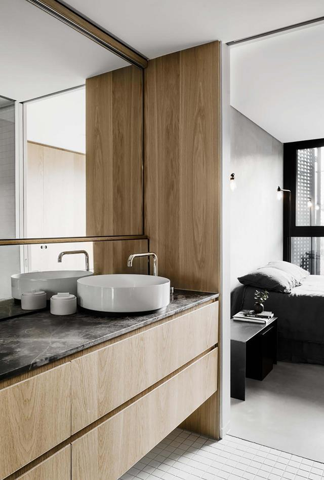 "Within a [industrial-style abode](https://www.homestolove.com.au/small-industrial-style-home-20242|target=""_blank""), the bathroom's timber joinery lends a note of warmth to the natural stone surfaces and adjoining bedroom's sleek, utilitarian shades of grey."