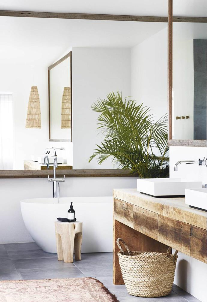 "Using recycled timber where possible was a must for the owners of this relaxed all-white [Byron Bay home](https://www.homestolove.com.au/relaxed-all-white-byron-bay-home-with-upcycled-details-19266|target=""_blank""). In the bathroom a recycled timber vanity is paired with twin white basins, white walls and a white freestanding bath tub."