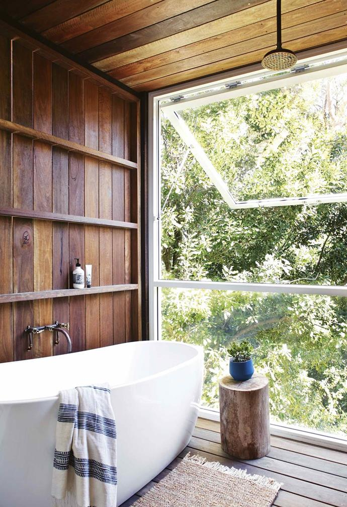 "Within this [beach house](https://www.homestolove.com.au/beach-house-noosa-18843|target=""_blank""), a rustic timber stump by the bath is perfect for a glass of wine and book, as well as a spot to perch. The raw timber echoes the panelled wall and green view outside."