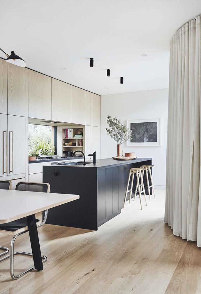 "The brief was clear: ""We wanted a clean, integrated look, so when you walk in it's not immediately obvious that it's a kitchen"", and the minimal black downlights of this kitchen in a [Scandi-noir coastal home](https://www.homestolove.com.au/scandi-noir-house-20344