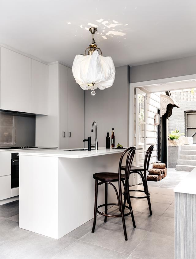 "A billowing pendant light is the centrepiece of this simple but classic kitchen in a [heritage-listed Sydney terrace](https://www.homestolove.com.au/redesign-of-a-heritage-sandstone-sydney-terrace-6317|target=""_blank""), drawing the eye up and accentuating an airy, spacious feeling in open living space."