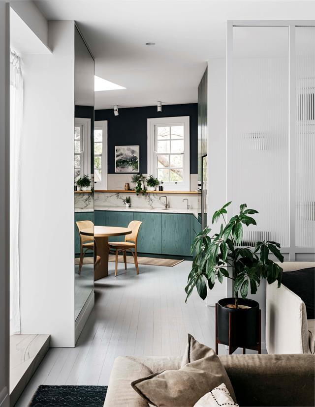 "A [triangular-shaped home](https://www.homestolove.com.au/modern-industrial-cafe-style-home-19429|target=""_blank"") in Sydney's Darlinghurst was given a modern-industrial, café-style makeover by Jonathon Richards. An indoor umbrella plant in the living room complements the green tones in the kitchen."