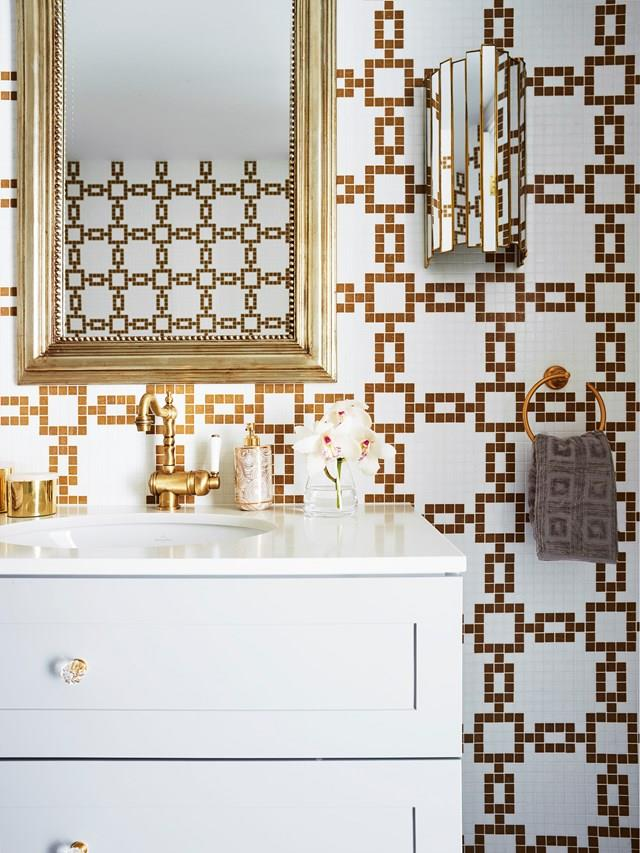 This glamorous powder room designed by Greg Natale features several Art-Deco motifs in the patter of the mosaic tiles, brushed brass tap ware and mirrored wall sconces.