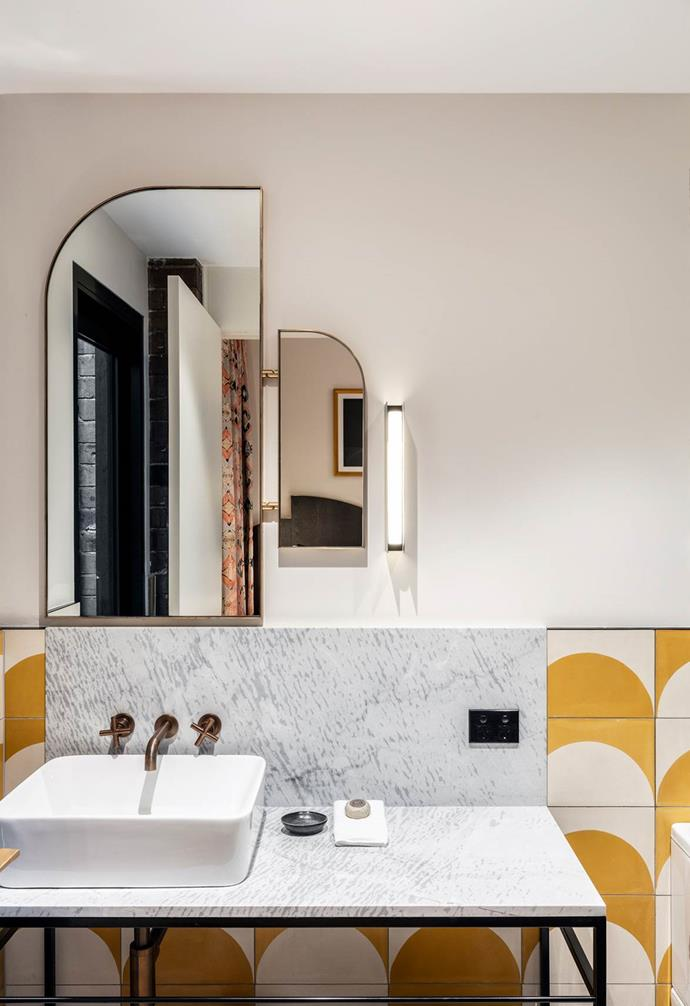 "Unconventional shapes in the [bathrooms of The Albion Hotel](https://www.homestolove.com.au/little-albion-guest-house-design-ideas-7166|target=""_blank"") adds an extra dimension and echos the Art-Deco love of unique geometrical angles. In this particular space, the top left curve of the mirror complements the round pattern of the tiles."