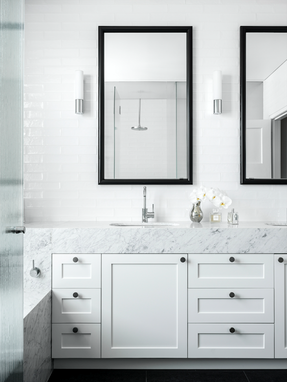 Subway tiles, Teranova. Carrara marble benchtop and bath surround. The custom mirrors conceal medicine cabinets. Wall lights, Zumtobel.