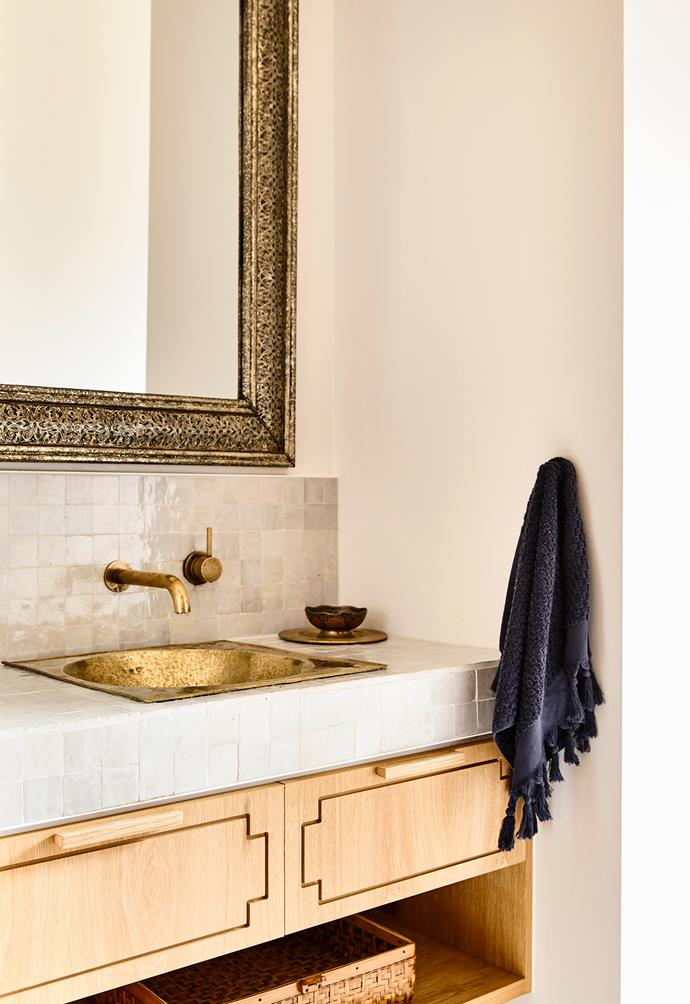 "In the [modern Mediterranean-inspired home of interior architect Georgia Ezra](https://www.homestolove.com.au/modern-mediterranean-style-home-5607|target=""_blank""), the bathroom has been partitioned with a door, splitting it into a chic powder room space, and a wash room. In the powder room an ornate mirror complements the brass tapware and basin, while a timber vanity adds warmth to the tiled benchtop.<br><br>"