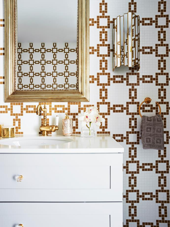 "The mosaic wall tiles in the powder room of this [glamourous Sydney home](https://www.homestolove.com.au/a-glamorous-sydney-home-with-a-hollywood-feel-6572|target=""_blank"") make a bold impact, and are paired with a pared-back white vanity that features brass tapware. A chic framed mirror and mirrored wall-sconce provide the finishing touches.<br><br>"