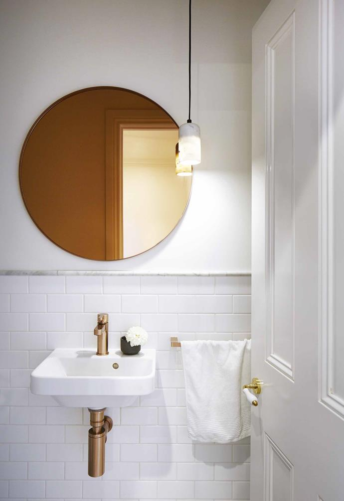 "Copper metallic tapware add a sense of luxury to this powder room in a [renovated semi-detached Edwardian home](https://www.homestolove.com.au/this-edwardian-semi-was-renovated-with-imagination-style-and-attention-to-detail-18524|target=""_blank""). The rose copper mirror adds a splash of colour in the mostly-white space.<br><br>"