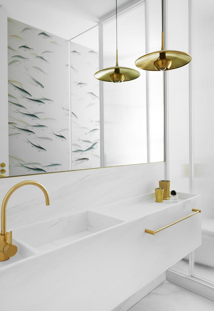 """In this [revamped mid-century home](https://www.homestolove.com.au/sensitively-revamped-mid-century-house-20728 target=""""_blank"""") the powder room was inspired by the idea of creating a """"jewel within a jewel"""", pairing an all-white palette with gleaming gold fixtures and de Gournay 'Fishes' wallpaper.<br><br>"""