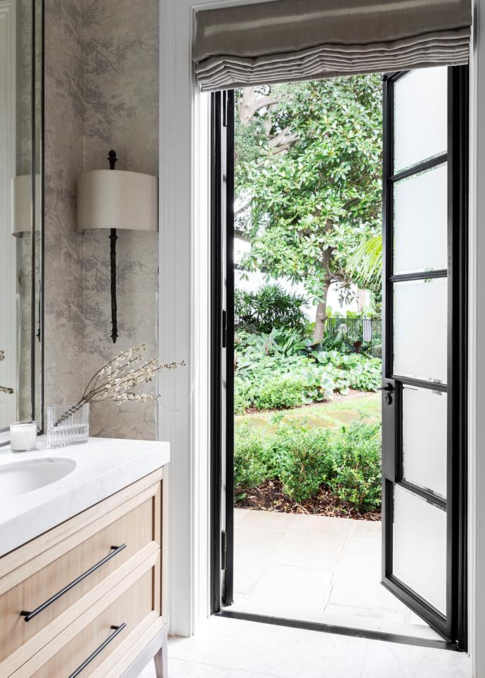 "The powder room in this [Georgian-style home](https://www.homestolove.com.au/georgian-style-home-inspired-by-obamas-residence-21091|target=""_blank"") opens to lush gardens and features a dramatic [steel-framed door](https://www.homestolove.com.au/steel-frame-doors-20439