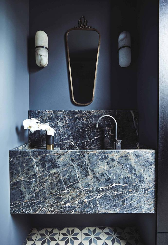 "A private, hidden part of the coastal home, the powder room in this [luxe coastal home](https://www.homestolove.com.au/luxe-coastal-home-with-spectacular-views-20953|target=""_blank"") boasts dramatic dark stone surfaces and the glamour of a vintage mirror. The twin wall sconces add a striking touch while the marble vanity is the crowning feature of the space.<br><br>"