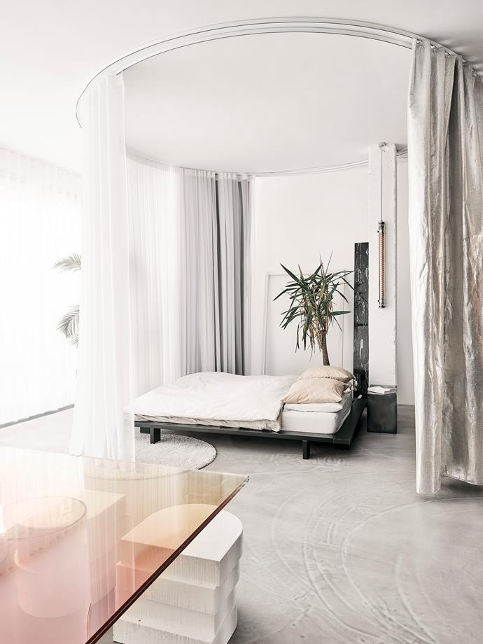 The bedroom is separated from the dining area by double-tracked curtains that Sabine constructed herself from fabrics used in greenhouses to control lighting conditions.