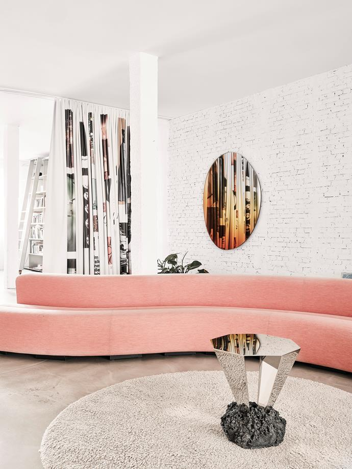 A sectional Pierre Paulin 'Osaka' leisure sofa by La Cividina in pink Febrik upholstery takes centre stage. Its undulating, organic lines contrast with the exposed brick walls and heated cement flooring. The Diamond table in concrete and mirrored steel is by Danish artist FOS, and the colourful dividing curtain is the work of Ehssan Morshed Sefat. The Off Round Hue mirror on the wall is by Sabine and Brit van Nerven.
