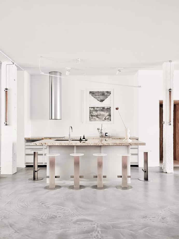 Designed by homeowners Sabine and Paul, the kitchen combines stainless steel, acrylic and River Gold granite to create a modern palette, featuring stools designed by the couple, a pink Valentina Cameranesi sculpture on the island, cylindrical extractor and Sammode glass tube lights.