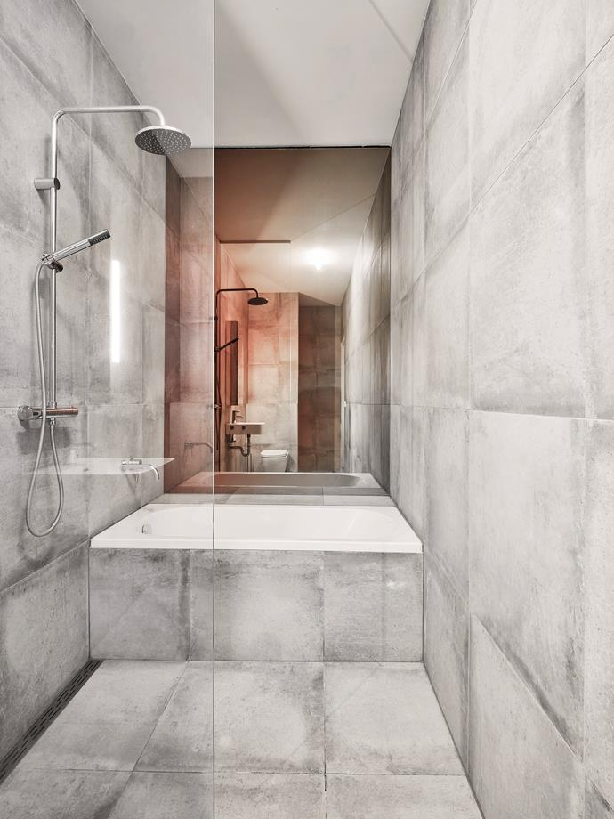 Inspired by Brutalist architecture, the bathroom is encased in large concrete tiles. The mirror was repurposed from an old commercial project, the colours echoing those of the dining table.
