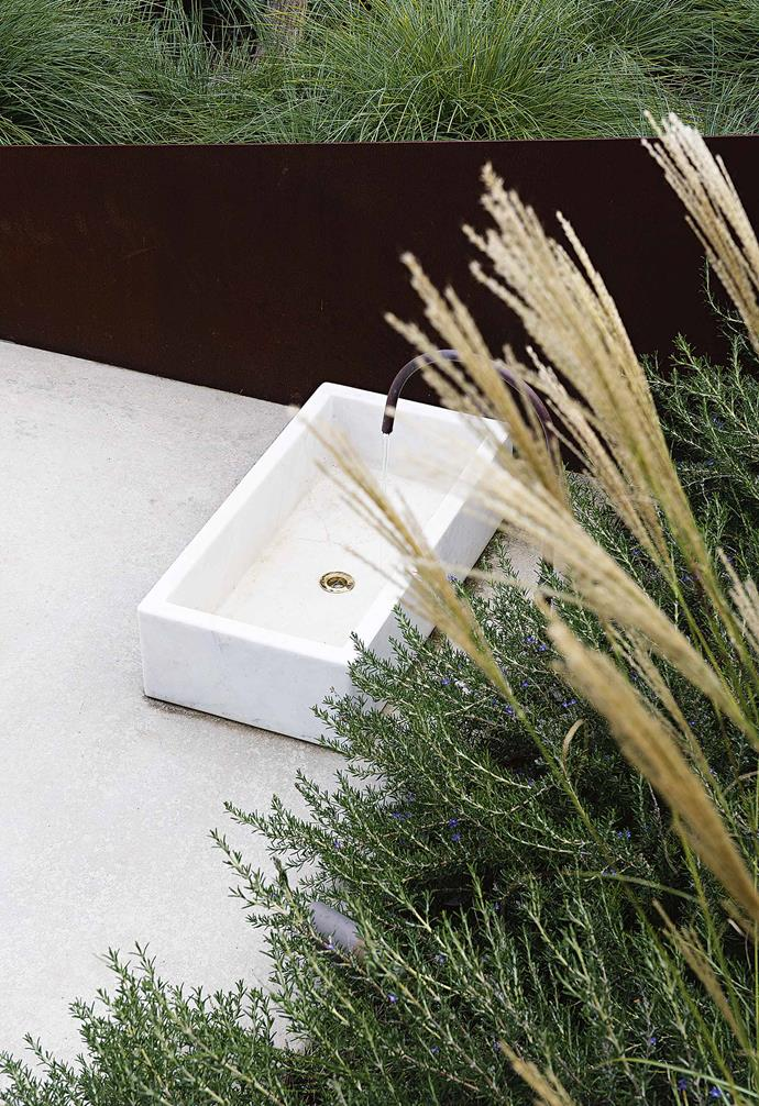 **SINK INTO IT** A marble basin adds a touch of luxury to the post beach-walk foot wash. The basin combines practicality and elegance, offering a welcome respite in summer after yet another beach visit. To top it off is the simple copper pipe spout, bent into a smooth gentle curve on site.